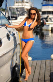 Model on the pier next to motorboat — Stock Photo