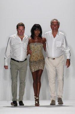 James Mischka (L) and Mark Badgley walk the runway with Naomi Campbell at the Badgley Mischka show