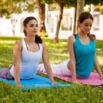 Girls practicing cobra yoga pose — Stock Photo #52643821