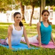 Girls practicing cobra yoga pose — Stock Photo #52643823