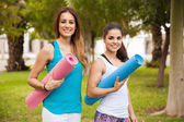 Women carrying yoga mats — Stock Photo