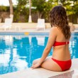 Young woman sitting near pool — Fotografia Stock  #56728897