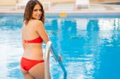 Young woman walking inside pool — Stock Photo