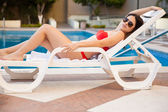 Young woman relaxing on a poolside chair — Stock Photo