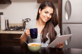 Woman with tablet, coffee, and cereal — Stock Photo