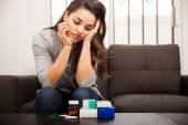 Overwhelmed woman with assorted medicines — Stock Photo