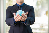Businessman holding globe in hands — Stock Photo