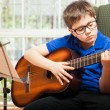 Little boy playing the guitar at home — Stock Photo #67248389