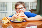 Boy enjoying a hamburger — Stock Photo