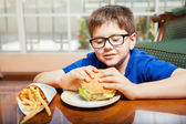 Boy in glasses eating junk food — Stock Photo