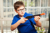 Boy playing with a toy rifle — Stock Photo