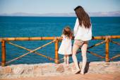 Woman and  girl looking at ocean — Stock Photo