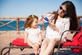 Mom and daughter putting sunblock on — Stock Photo