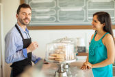 Employee in an apron selling some cookies — Stock Photo