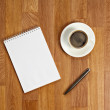 Blank notepad with office supplies and cup of coffee on wooden t — Stock Photo #52397067