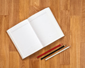 Blank notepad with office supplies on wooden table. — Photo