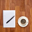 Blank notepad with office supplies and cup of coffee on wooden t — Stock Photo #54262901