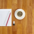 Blank notepad with office supplies and cup of coffee on wooden t — Stock Photo #59193729