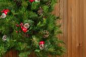 Fragment av grön dekorerad julgran på trä bakgrund. — Stockfoto