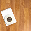 Blank notepad with office supplies and cup of coffee on wooden t — Stock Photo #59546497
