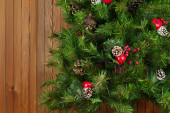 Fragment of Green Decorated Christmas Tree on Wooden Background. — Stock Photo
