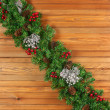 Garland with Christmas ornaments and pine cones on wooden backgr — Stock Photo #60294487