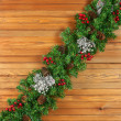 Garland with Christmas ornaments and pine cones on wooden backgr — Stock Photo #60755407
