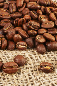 Roasted coffee beans on burlap background. — Stock Photo