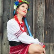 Woman wearing national ukrainian clothes sitting in wooden hut — Stock Photo #52411765
