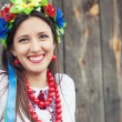 Woman wearing national ukrainian clothes sitting in wooden hut — Stock Photo #52411781