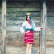 Woman wearing national ukrainian clothes near wooden hut — Stock Photo #52411841