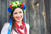 Woman wearing national ukrainian clothes sitting in wooden hut — Stock Photo