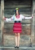 Woman wearing national ukrainian clothes near wooden hut — Stock Photo