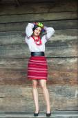 Woman wearing national ukrainian clothes near wooden hut — Stock Photo