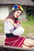 Çizilmiş eski at üzerinde ahşap sepeti oturuyor Ulusal Ukrayna elbise giyen kadın — Stok fotoğraf