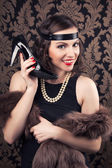 Woman holding a black shoe like phone receiver — Stock Photo