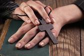 Hands holding vintage cross on Bible — Foto de Stock