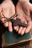 Hands holding vintage cross on Bible — Stock Photo