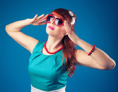 Girl posing with red heart-shaped sunglasses — Stock Photo