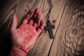 Old cross and bloody hand — Stock Photo