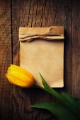 Yellow tulip with notepad — Stock Photo