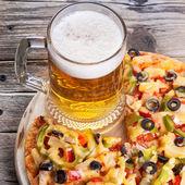Smakelijke pizza met een glas bier — Stockfoto