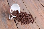 Cup with coffee beans on a wooden table — Stock Photo