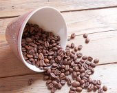 Cup and beans on a wooden table — Stock Photo