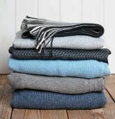 Stack of warm woolen clothing on a wooden table — Stock Photo