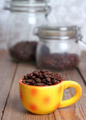 Orange cup with coffee beans — Photo