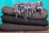 Stack of grey and black blue jeans with scarf on a wooden table — Photo