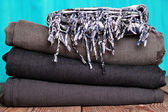 Stack of grey and black blue jeans with scarf on a wooden table — Foto Stock