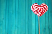 Heart shaped lollipop for Valentine's Day with turquoise backgro — Stock Photo