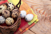 Quail eggs in a wicker basket on a wooden background with napkin — Stock Photo